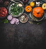 Food background for healthy vegetarian cooking ingredients for tasty pumpkin dishes recipes in bowls : tomato sauces, spinach, sliced onion, pumpkin seeds, top view, banner. Clean seasonal eating