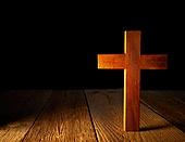 Christian wood cross on black and wooden background