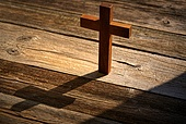 Christian cross on wood over wooden background vintage with shadows