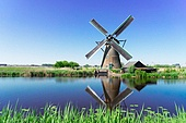 traditional dutch windmill with reflection at Kinderdijk at summer day, Netherland. dutch windmill over river waters