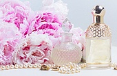 Wedding lifestyle with fresh pink peony flowers, glamour bottles and jewellery close up. Wedding lifestyle with peony flowers