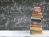 stack of books on white wooden table with math formulas on blackboard. set of books