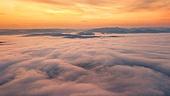 Beautiful foggy dawn in mountains. Sea of fog between mountain peaks. Carpathian mountains, Ukraine.