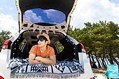 남성, 차박캠핑 (캠핑), 캠핑, 휴가, 혼자여행 (여행), 엎드림 (눕기), 자동차트렁크 (교통수단일부), 엷은색선글라스 (선글라스), 미소