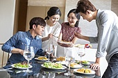 Young Chinese friends dining together at home