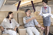Chinese flight attendant serving wine to mature couple