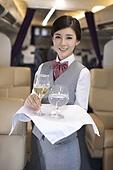 Chinese flight attendant serving wine
