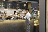 Happy Chinese couple working in coffee shop