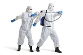 Young Chinese people in protective suit using crop sprayer