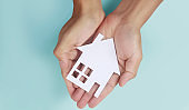 Hands holding paper house, family home protecting insurance concept