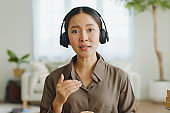 POV Young Asian woman wearing headphone talking on video call conference or virtual meeting on laptop computer work from home