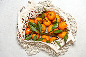White mesh bag full of tangerines with leaves. Top view.