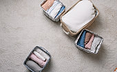 Neatly folded clothes in open organizer boxes, top view. cleaning method