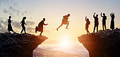 Challenge of business concept. Group of businesspeople climbing a mountain. Teamwork. Success.