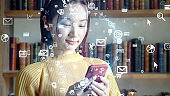 Young asian woman using a smart phone. Communication network concept. IoT (Internet of Things). Telecommunication.