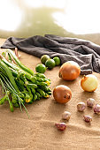 Green vegetable ingredients lime garlic onion on vintage sunny day light background setup