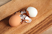 Chef peeling boiled egg on wooden cutting board in kitchen