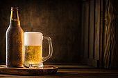 Beer bottle with a drinking glass full of beer on a rustic wooden table