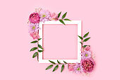 Square flower frame made of rose, aster and alstroemeria on a pink pastel background.