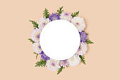Wreath made of dahlia and green leaves on a beige background.
