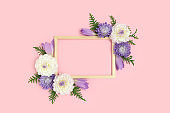 Top view of flower frame made of dahlia on a pink pastel background.
