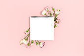 Blank notepad mockup with frame made of flowers. Greeting card concept on a pink pastel background.