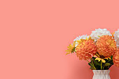 Bouquet of dahlia flowers in vase in front of coral background.