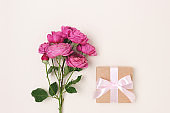 Gift box with a tied bow and bouquet of rose flowers on a beige background.