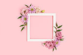 Square flower frame made of eustoma on pink background.
