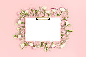 Clipboard mockup with blank paper card. Frame made of flowers on a pink pastel background.