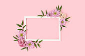 Empty flower frame made of eustoma on a pink pastel background.
