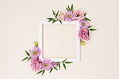 Square flower frame made of pink eustoma on a beige background. Greeting card template with copyspace.