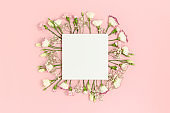 Blank paper card mockup with copy space. Frame made of flowers on a pink pastel background.