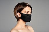 Young girl with black reusable virus protective mask