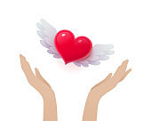 Female hands releasing red heart with wings