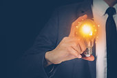 Businessman holding light bulb, imagination and intelligence, innovation and inspiration, brain symbol and solution and knowledge, creative idea and success, business and marketing concept.