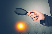 Businessman holding magnifying glass for search idea with light bulb with bright is metaphor, innovation and inspiration, solution and imagination, decision and choice for success, business concept.