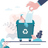 Hand puts medical mask in trash can. Recycling of personal protective equipment. Trash bin full of face masks and gloves