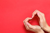 Valentine's day concept. A young girl shows a heart sign with her hands on a red background. Copy space top view.