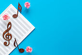 Musical wooden notes on music sheet. Top view