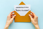 Hands holding award congratulation card in golden envelope. Text You're a winner in letter