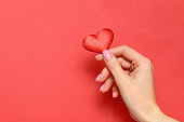 Valentine's day concept. A young girl holds a heart in her hand on a red background. Copy space.