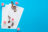 Musical wooden notes on music sheet with flowers. Top view