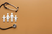 Wooden family figure with stethoscope. Life and health insurance concept