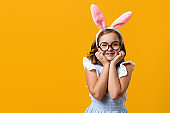Happy easter. Cheerful little girl in a rabbit costume. Cute child on a yellow background.