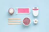 Set of epilation means - epilator with wax strips, razor and flowers. Top view