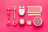 Cosmetics set for epilation with epilator and wax strips and flowers. Top view
