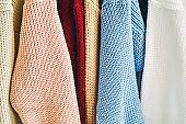 multicolored women's woolen sweaters on hangers. Sale in a fashion store