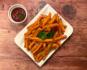 Crispy and crunchy sweet potato fries with a bowl ketchup.