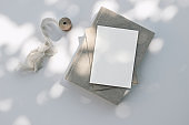 Summer wedding stationery still life scene. Old book, blank greeting card, invitation mockup and craft envelope in sunlight. White table background with ribbon. Harsh long shadows. Flat lay, top view.
